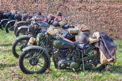 Green military motorcycles parked in a row. Green army military motorcycles parked in a row on green grass in front of brown hedge Royalty Free Stock Photography
