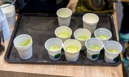 Green milke tea sample in mini white plastic tasting cup on black tray. Marketing promotion for new launched flavor of healthy product stock image