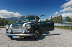 Green Mini Cooper on a sunny day. A Limited Edition Mini Cooper with a door open and the blue sky in the background royalty free stock images