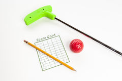 Green mini golf club with score card and ball. Green mini golf club with score card, pencil  and red ball Royalty Free Stock Image