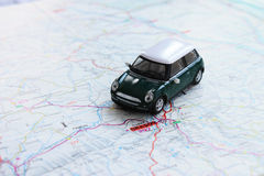 Green miniature car on paper map. Green miniature car on road paper map Stock Photography