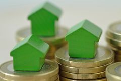 Green miniature houses on coin stacks - Concept of real estate investment, mortgage, home insurance and loan, eco-friendly house. Green miniature houses on coin stock photo
