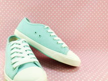 Green mint sneakers for lady with pink polka dot background Royalty Free Stock Images