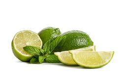 Green mint, two limes and two slices of a juicy lime. On white background royalty free stock images