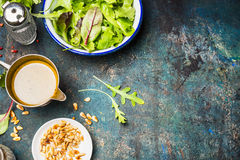 Green mix salad with oil dressing and pine nuts on rustic background Stock Photo