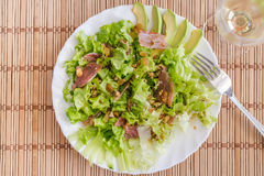 Green mix salad plate with avocado, prosciutto, raisins and pecans over bamboo mat Stock Image