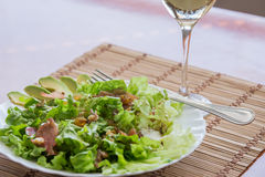 Green mix salad plate with avocado, prosciutto, raisins and pecans over bamboo mat Royalty Free Stock Image