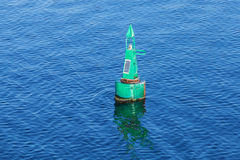 Green modern navigation buoy on sea water Royalty Free Stock Photo