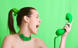 Green monster. Woman on green background screaming into the green phone Royalty Free Stock Photography