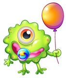A green monster baby with a balloon Royalty Free Stock Photo