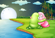 A green monster comforting the pink monster at the riverbank Royalty Free Stock Photography
