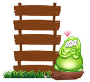 A green monster beside the empty wooden boards Royalty Free Stock Images