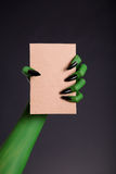 Green monster hand with black nails holding blank piece of cardb Royalty Free Stock Image