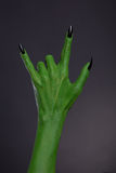 Green monster hand with black nails showing heavy metal gesture. Studio shot on black background stock image