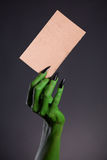 Green monster hand holding blank piece of cardboard Royalty Free Stock Photo