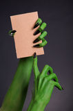 Green monster hands with black nails holding blank piece of card Stock Photo