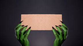 Green monster hands with black nails holding empty piece of card Royalty Free Stock Photography