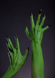 Green monster hands with black nails stretching up, real body-art. Halloween theme stock photos
