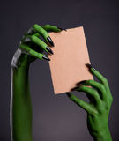 Green monster hands holding empty piece of cardboard stock photo