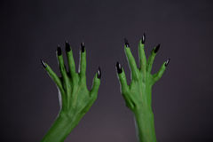 Green monster hands with sharp black nails, body-art Stock Photos