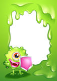 A green monster with a shield standing in front of an empty temp Royalty Free Stock Photography