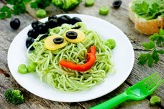 Green monster spaghetti - pasta with green vegetables in the for. M of funny Frankenstein, tasty and healthy dish for children Stock Image