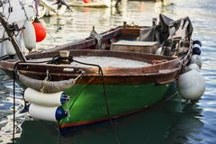 Green moored fishing boat with fenders. Green wooden fishing boat with fenders moored by ropes in the sea at the berth royalty free stock photo
