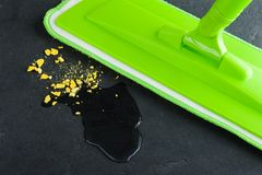 Green mop mopping black concrete floor. With water Stock Photos
