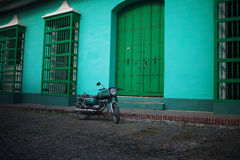 Green motorcycle on the street, on background of green houses, color effect Royalty Free Stock Images