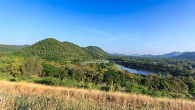 The green mountain and brown grass at foreground with blue sky background stock video