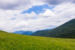Green mountain meadow with mountain range, northern Slovakia. Mountain landscape with meadows, forest, hills and blue sky, Slovakia royalty free stock images