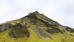 Green mountain near Skogafoss waterfal in Iceland. Travel to Iceland - green mountain near Skogafoss waterfall in Katla Geopark on Icelandic Atlantic South Coast Stock Photography