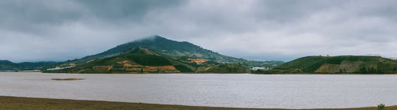 Green Mountain Beside Ocean during Cloudy Day Royalty Free Stock Photography