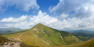 Green mountain peak with clouds. A top of green mountain peak with a path and white clouds Royalty Free Stock Photos
