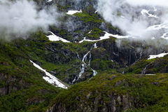 Green mountain slope with snow and waterfalls Royalty Free Stock Image