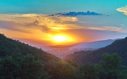 Free Green Mountain Slopes Covered With Thick Trees Against The Backdrop Of The Beauty Of The Setting Sun Are Blazing With Stock Photo - 120656090