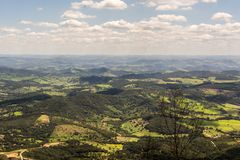 Green mountainous landscape with partially clouded sky. Aerial view of green hilly landscape in rural Brazil. A twig is seen on the background, and sparsely royalty free stock image