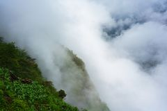 Green mountains cliff and low white clouds royalty free stock image