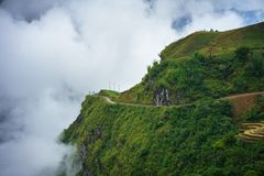 Green mountains cliff and low white clouds stock images