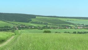 Green mountains (meadows), blue sky and village, the UNESCO Bile Karpaty stock video footage