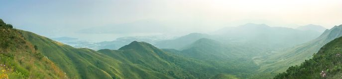 Green mountains and ocean in panorama view. The green mountains and ocean in panorama view Royalty Free Stock Photos