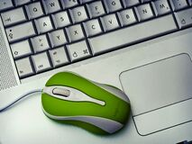 Green Mouse on silver Laptop Stock Photo