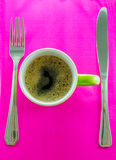 Green mug with coffee on saucer with cutlery. Green mug with coffee erroneously with cutlery on pink background Stock Photo