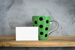 Green mug with dots and blank card on wood Stock Images