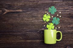 Green mug with four-leaf clover on wooden background. Copy space. Top view.  St.Patrick`s day holiday symbol Royalty Free Stock Photos