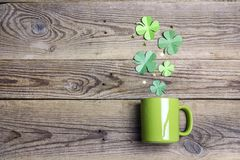 Green mug with four-leaf clover on wooden background. Copy space. Top view. St.Patrick`s day holiday symbol stock image