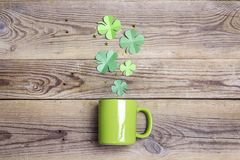 Green mug with four-leaf clover on wooden background. royalty free stock photography