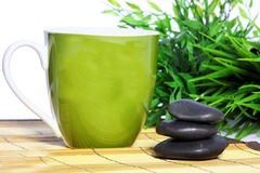 Green mug and spa massage stones Royalty Free Stock Photos