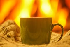 Green mug for tea or coffee, wool things near cozy fireplace, wi Royalty Free Stock Photos