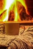 Green mug for tea or coffee, wool things near cozy fireplace, wi Stock Photography
